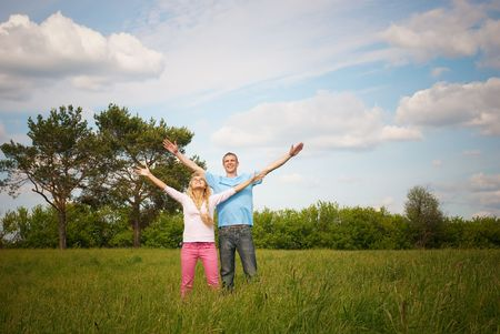 arms wide: Couple standing on grass with raised arms. Stock Photo