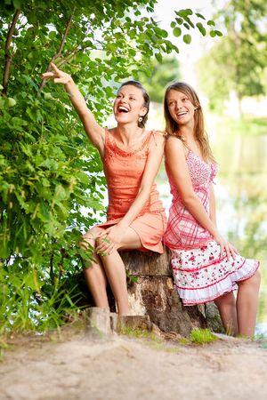 Two laugh teenage girls on stub about lake. photo