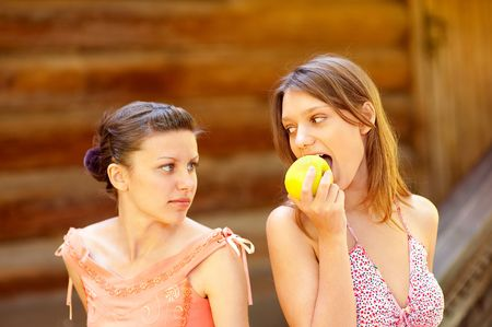 Beautiful young girl taking a bite of an apple. Other girl wishes to eat apple too. Stock Photo - 6553200