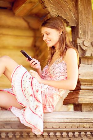 log hair:  Young woman using her phone at wooden log hut. Stock Photo