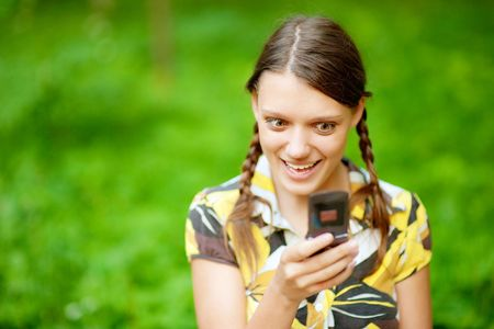 Young woman using her phone at  park. photo