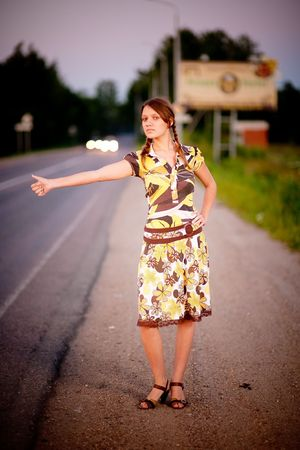 Young beautiful woman hitchhike against evening city street. photo