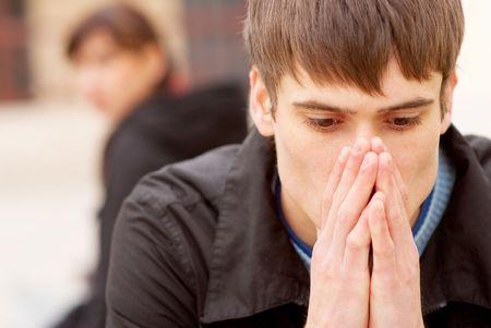 smutny mężczyzna: Wściekły para siedzi na stanowisku badawczym w mieście.  Zdjęcie Seryjne
