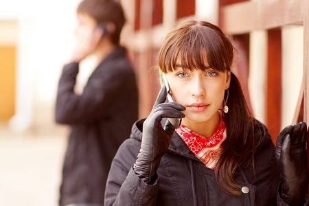 cellular telephone: Young beautiful people talk on cellular telephone in city. Stock Photo