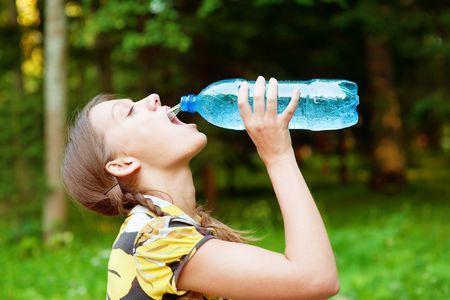 Pretty woman drinking water on summer glade Stock Photo - 6512805