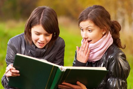 Two young attractive women reading a book in a park. photo