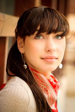 Beautiful girl with kerchief on neck against wooden handrail. photo