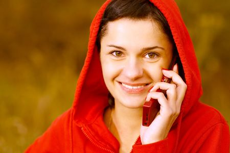 Girl in  autumn park speaks by phone. Stock Photo - 6538587