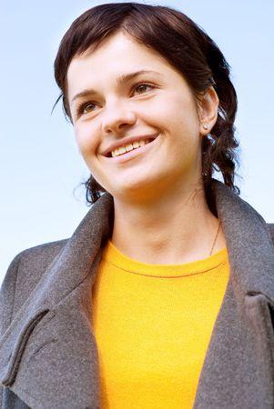 Portrait of beautiful smiling brunette girl against blue sky. photo