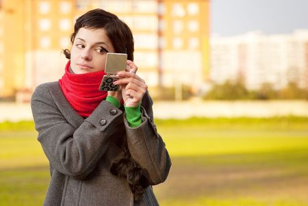 Girl with red scarf looks in mirror against autumn. photo