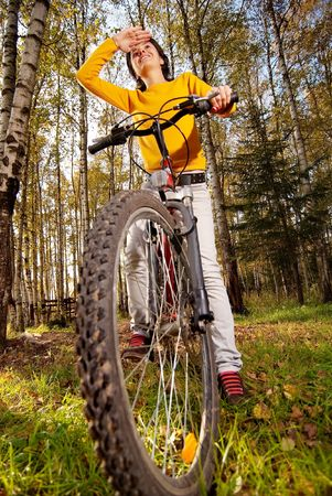 Beautiful girl riding bicycle against autumn nature. Stock Photo - 6552665