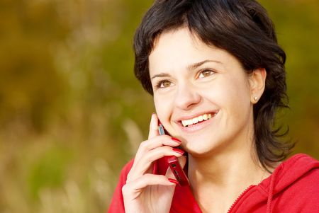 Girl in  autumn park speaks by phone. Stock Photo - 6552670