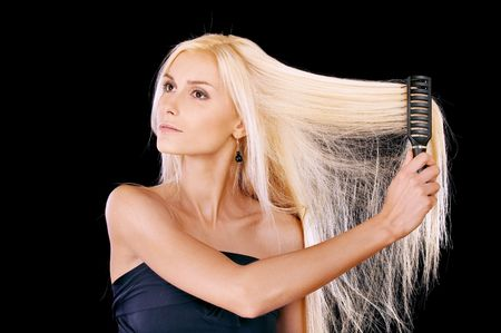 Nice young woman combs hair, it is isolated on black background. Stock Photo - 6610107