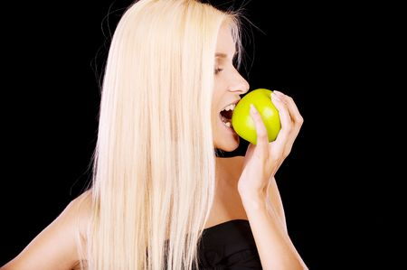 Woman eating green apple, isolated on black background. photo