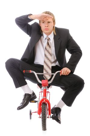 Businessman goes on childrens bicycle, isolated on white background. photo
