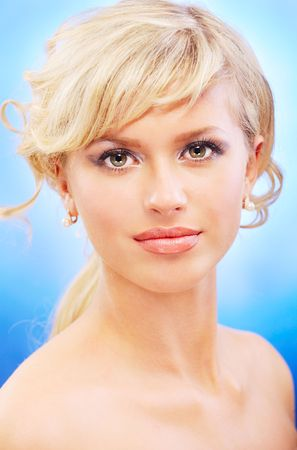 Portrait of charming blonde, on blue background. photo