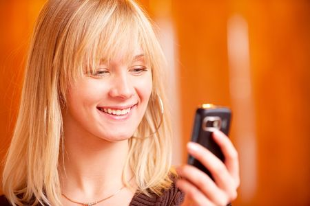 Charming girl reads sms on mobile phone and smiles. Stock Photo - 6663011