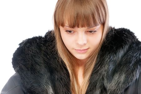 Beautiful young woman in winter fur coat, isolated on white background. photo