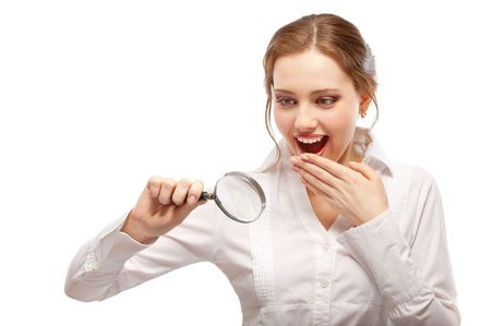 Amazed girl looks through magnifier, isolated on white background. Stock Photo - 6663055