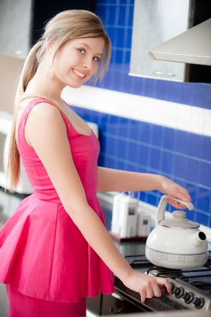 Girl in red dress holds teapot and includes gas cooker photo
