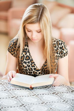 Girl-student reads book in spacious room. photo
