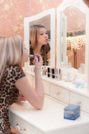 Girl sits before three-leaved  mirror and paints lips with lipstick photo