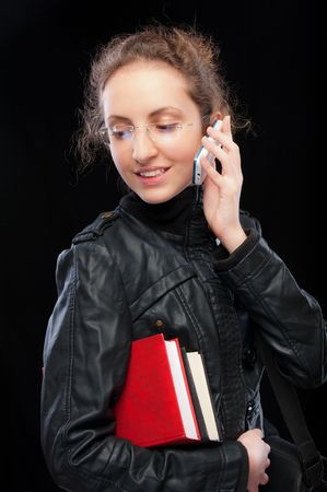 speaks: Young student holds books and speaks by cellphone.
