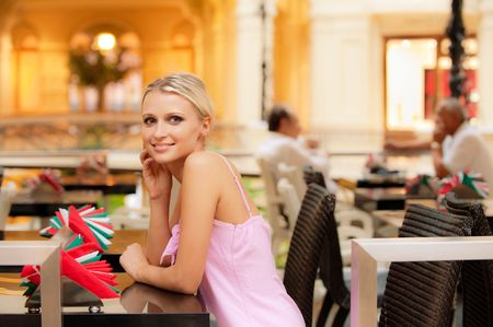 Smiling nice girl sits at little table at restaurant. photo