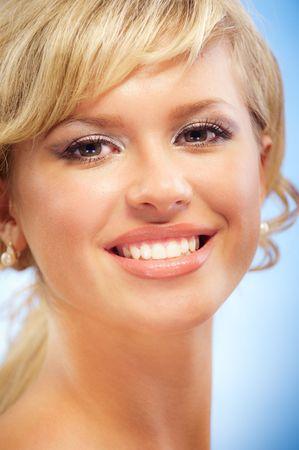 bared teeth: Portrait of charming smiling blonde on dark blue background