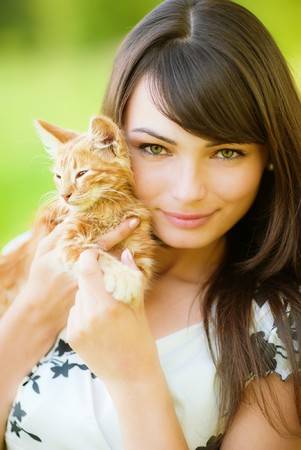 red head girl: Beautiful girl holds on hands of kitten. Stock Photo