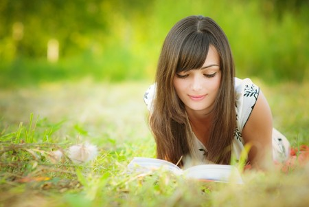 Beautiful girl lies on meadow and reads the book photo