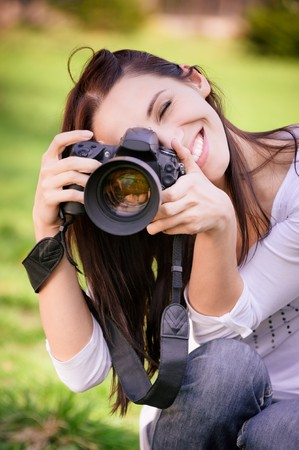 human photography: Beautiful smiling girl with camera on nature.