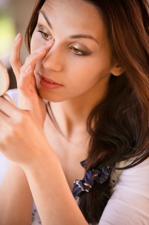 Young woman looks in mirror and corrects make-up. Stock Photo - 6977243