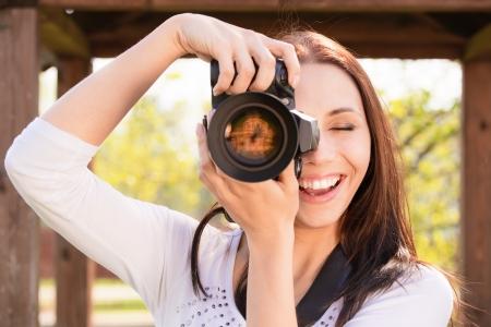 human photography: Hermosa ni�a sonriente con la c�mara en la naturaleza. Foto de archivo