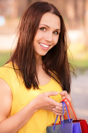 Beautiful girl in yellow clothes with purchases against summer nature. photo