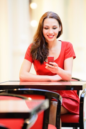 Beautiful smiling girl in red dress sits in cafe and reads sms on phone. photo