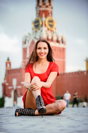 Young beautiful woman sits on Red Square, Moscow, Russia, photo