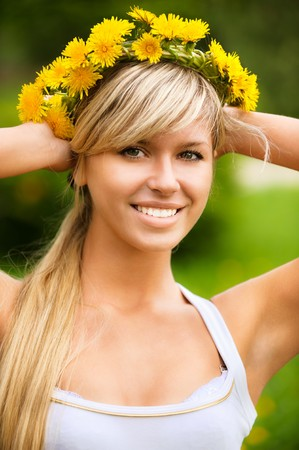 sprightly: Young woman in wreath from yellow dandelions.