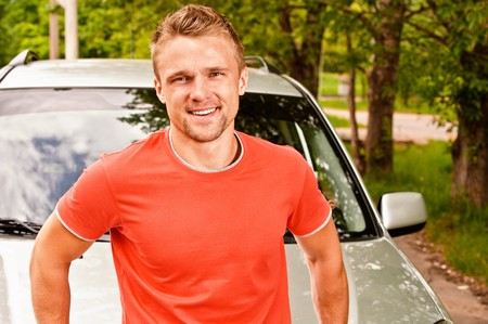 cowl: Driver of car stands about cowl and smiles against summer nature. Stock Photo