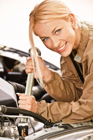 Woman car mechanician repairs engine of car and smiles. Stock Photo - 7048942