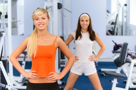 sport hall: Two beautiful smiling sportswomen do exercises in big sports hall. Stock Photo