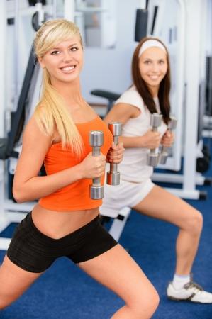 salle de sport: Deux jeunes sportives � beau sourire font des exercices avec halt�res dans la salle de sport big.  Banque d'images