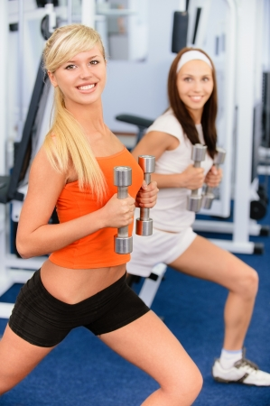 Two beautiful smiling sportswomen do exercises with dumbbells in big sports hall. Stock Photo