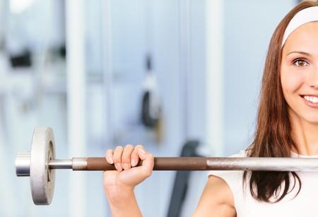 salle de sport: Jeune femme ascenseurs poids et sourires, contre la salle de sport.