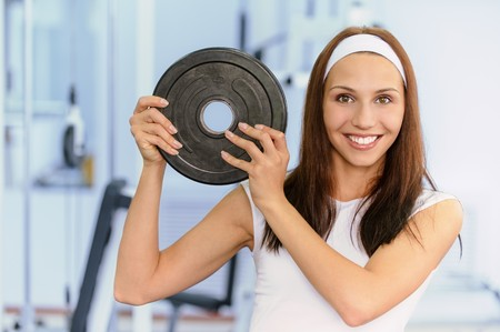 Young woman lifts weight and smiles, against sports hall. Stock Photo - 7048991