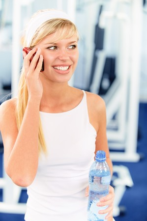 sport hall: Young smiling fair-haired sportswoman talks by mobile phone against big sports hall.