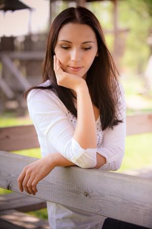 naar beneden kijken: Lachende jonge vrouw zitten op houten bench en look.