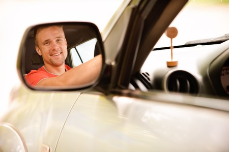 Smiling driver is reflected in mirror of car.