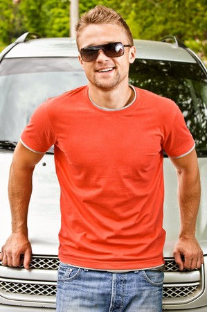 cowl: Driver in sun glasses of car stands about cowl and smiles against summer nature. Stock Photo