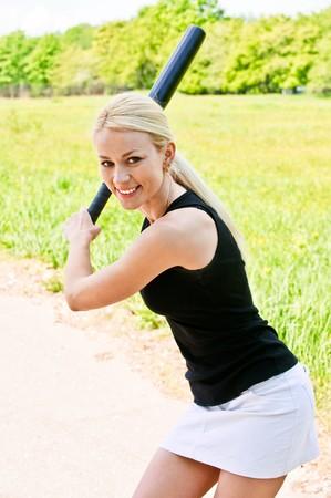 Sportswoman with baseball bat against summer city park. photo